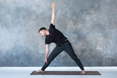 Man beginner practicing yoga doing trikonasana pose. royalty free stock images