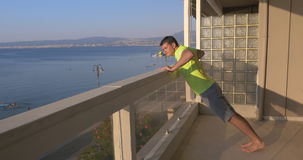 Man beginning push ups on the balcony with sea view background stock video
