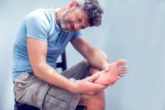 Man begreppet som för handen den hållande foten med smärtar, hälsovård- och läkarundersökning royaltyfria foton