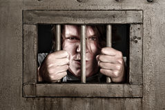 Man behind bars. Man in prison holding the bars of his cell door Royalty Free Stock Image