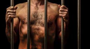 Man behind bars. Nude man behind the bars of prison stock photos