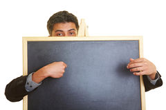 Man behind blackboard. Man hiding behind a blackboard royalty free stock images