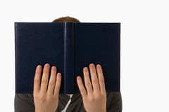 Man behind book. Young man engrossed in his book Royalty Free Stock Photography