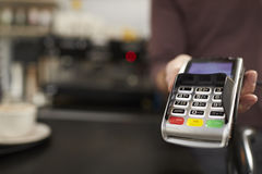 Man behind cafe counter offers credit card reader, close up Royalty Free Stock Photo