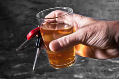 Man behind car key and glass of liqueur Royalty Free Stock Photos