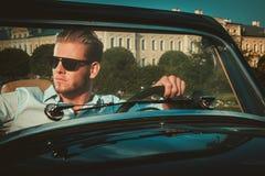 Man behind classic convertible steering wheel Royalty Free Stock Image