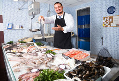 Man  behind counter holding fish Stock Photography