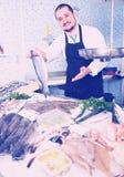 Man  behind counter holding fish Stock Photos