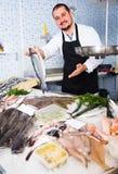Man  behind counter holding fish Royalty Free Stock Photo