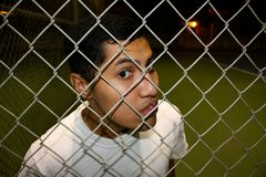 Mexican Immigrant. A young hispanic male looking through fence Stock Photography