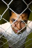 Mexican Immigrant. A young hispanic male looking through fence Stock Photos