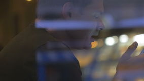 Man behind the glass browsing internet on mobile stock video footage