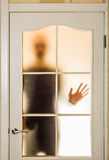 Man behind the Glass Door. Silhouette of an unknown man in black seen through a closed glass door, like a ghost or an alien stock image