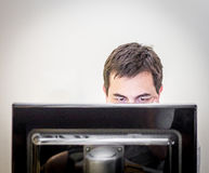 Man behind the monitor of a desk computer. Man with concentrated look eyes while hiding behind the monitor of a desk computer, with available copy space stock images