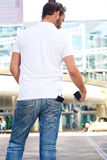 Man from behind with phone and power bank Stock Photos