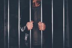 Man behind prison bars. Arrested criminal male person imprisoned Stock Images