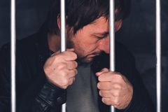 Man behind prison bars. Arrested criminal male person imprisoned stock photography