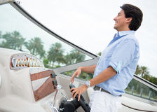 Man behind the wheel of a boat Royalty Free Stock Images