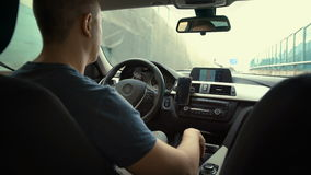 Man behind the wheel, seen from behind. The young man behind the wheel of a car stock video