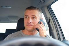The man behind the wheel sitting in the car. Takes a phone call. royalty free stock photos
