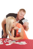 Man behind woman playing cards he is happy Stock Photos