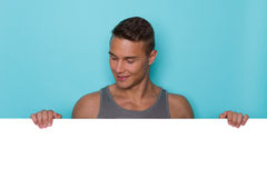 Man Behing Placard Is Reading It. Young attractive man in gray tank top standing behind big white placard, holding it, smiling, looking down and reading. Head Royalty Free Stock Photography