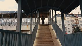A man with beige coat and backpack walking up the stairs of the footbridge stock video footage