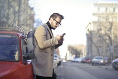 Man in Beige Coat Holding Phone Leaning on Red Vehicle Royalty Free Stock Image