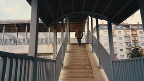A man with beige coat running up the stairs of the footbridge stock video footage