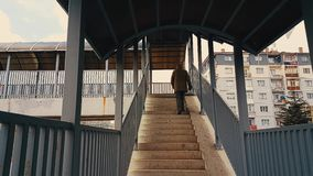 A man with beige coat walking up the stairs of the footbridge stock video footage