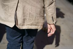 Man in a beige crumpled jacket. And blue pants walks down the street. View from the back Royalty Free Stock Images