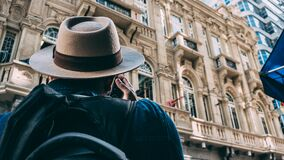 Man in Beige Hat Taking Picture on Beqige Conrete Architectural Building royalty free stock photo