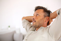 Man with beige shirt relaxing at home Stock Photos