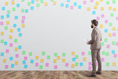 Man in beige in sticky notes room. Rear view of a businessman in beige looking at a wall covered by colored sticky notes and a blank piece. 3d rendering, mock up Royalty Free Stock Images