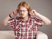 Man being annoyed with noise. Man being annoyed with loud noise having fingers in ears pretending to be deaf stock image