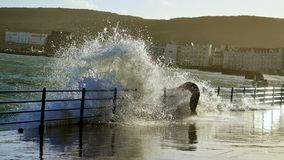 Man being hit by a wave. A man being hit by a wave on douglas, isle of man sea front Royalty Free Stock Image