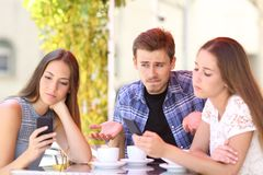 Man being ignored by his friends. Who are using their smart phones stock image