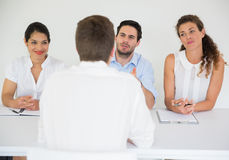 Man being interviewed by business people Royalty Free Stock Photo