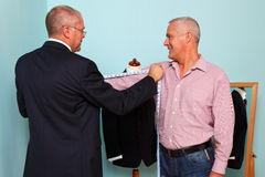 Man being measured for a bespoke suit. Photo of a tailor measuring a mans arm length during fitting for a new bespoke suit Stock Images