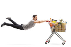 Man being pulled by a shopping cart full of groceries Stock Images