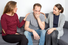 Man being sad in living room. Two women helping a male friend stock photos
