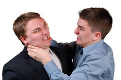 Man Being Strangled. Young man in a dress shirt strangling a young man in a business suit. Isolated stock photography