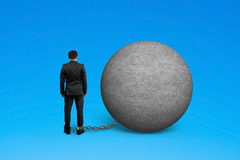 Man being trapped with concrete ball. Isolated on blue Stock Images