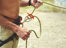 Man belaying other climber through a belay device. Stock Photography