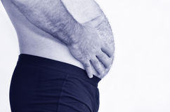 Man with belly assessing his weight. Man holds his belly and assessing his weight against white background with copy space. Concept photo of male health problems Stock Photos