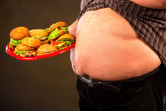 Man belly fat with hamberger fast food for overweight person. Man belly fat with hamberger group fast food . Breakfast for overweight person. Cropped shot of Stock Image