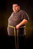 Man belly fat with tape measure weight loss around body . Man belly fat with tape measure weight loss around body on black background Stock Image