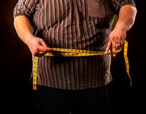 Man belly fat with tape measure weight loss around body . Man belly fat with tape measure weight loss around body on black background. Cropped shot of first day Stock Photo