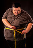 Man belly fat with tape measure weight loss around body . Man belly fat with tape measure weight loss around body on black background. First day of diet Royalty Free Stock Photography