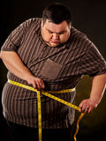 Man belly fat with tape measure weight loss around body . Man belly fat with tape measure weight loss around body on black background. First day of diet. Person Stock Image